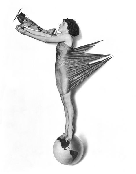 1927 pinup girl standing on globe with model of plane in her outstretched arms