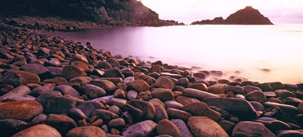 Aragunnu Beach at sunrise, with beach stones polished by water. Mimosa Rocks National Park, New South Wales, Australia