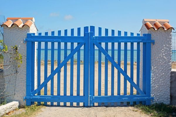 Blue gate to the Giunco beach. San Pietro Island, Sardinia, Italy