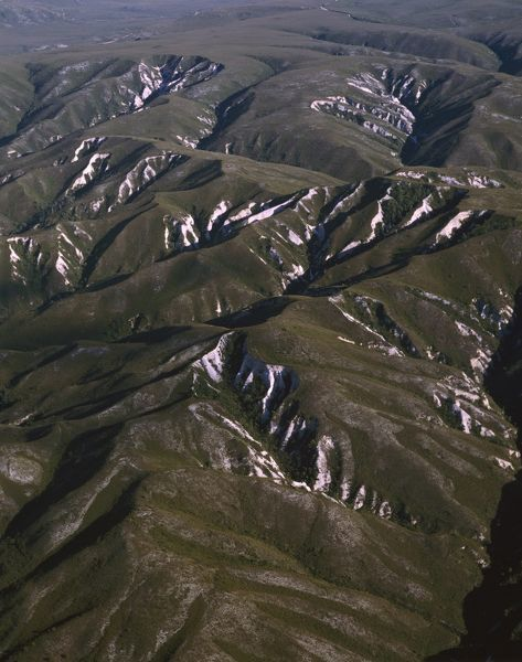D'Aguilar Range foothills with remnant snow drifts, aerial photograph. Southwest Conservation Area, Tasmania, Australia