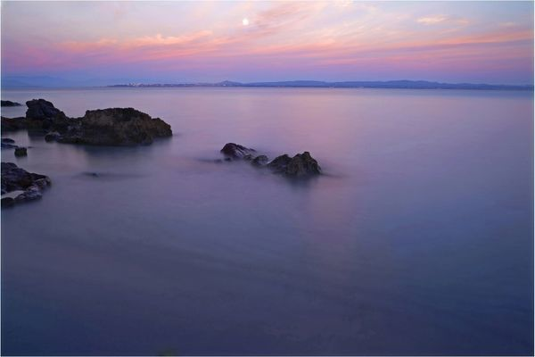 The Moon in sunset afterglow, and rocks in a still Mediterranean Sea. San Pietro Island, Sardinia, Italy