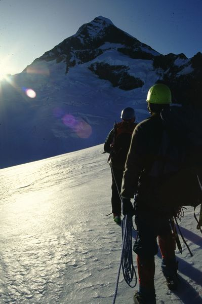 Mountaineers making their way along northwest ridge at sunrise. Mount Aspiring National Park, New Zealand