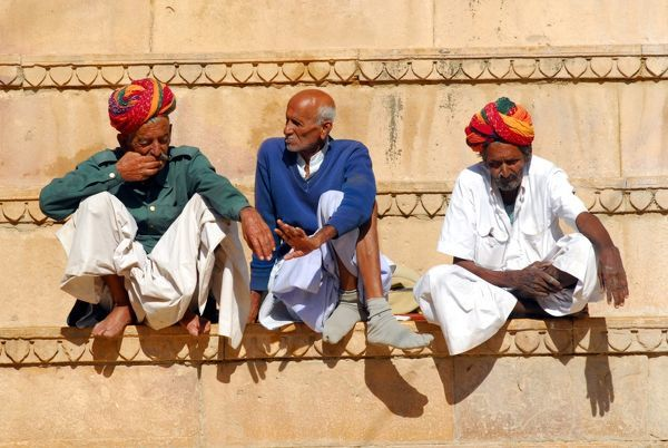 Three Rajasthani gentlemen whiling away a morning on a bench built into the wall of the Fort. Jaisalmer, Rajasthan, India