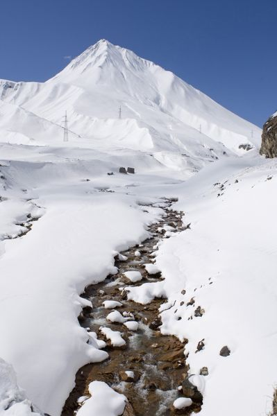 A stream flowing in a snow-covered mountain valley. Greater Caucasus Mountains, Georgia
