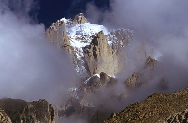 Summit crags of Paiju Peak, 6610 m, in cloud. Karakoram Range, Baltoro region, north Pakistan