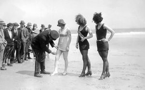1921: police officer on beach checking length of bathing suits