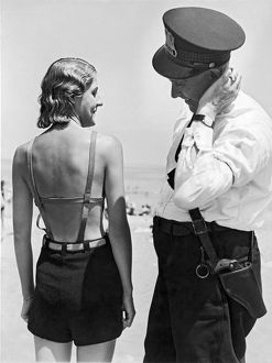 1927: A policeman contemplates the latest style in bathing suit