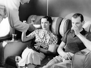 1936: couple being served cocktails on board Imperial Airways Em