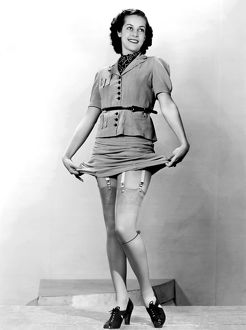 1940: young woman modelling nylon stockings and suspenders