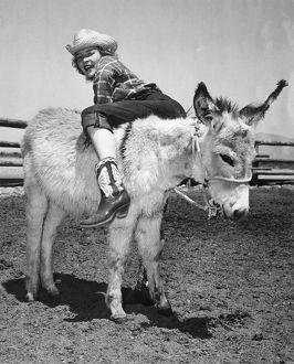 1947: cowgirl climbing onto donkey backwards