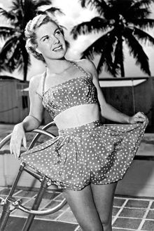 1950: young woman modelling silk swimming costume mimicking baby