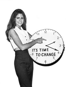 1964: woman hlding clock with the message a€™Ita€™s time to chan