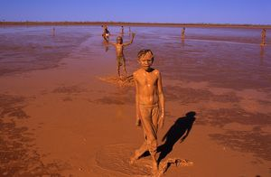 Aboriginal children larking in mud