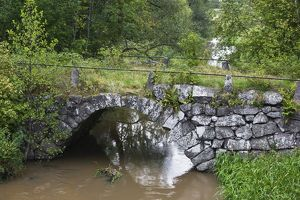 Arched stone bridge over stream in summer,
