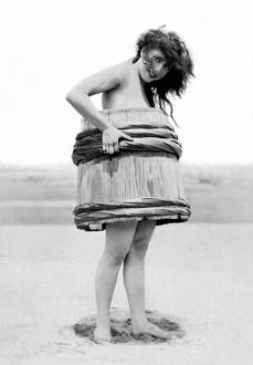 ca 1915: cheeky woman on beach wearing nothing by a barrel