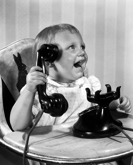 ca: 1930: a toddler enthusiastically holds a phone up to his ear