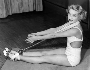 ca 1933: young woman exercising indoors using apparatus