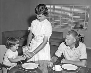 ca 1955: family scene with mother pouring milk for young child w
