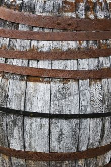 Closeup of old wooden barrel with rusty hoops,