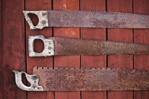 Collection of rusty saws as decoration on exterior timber wall,