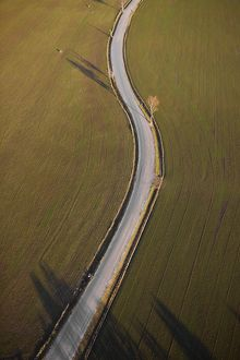 Country road curving through farmland,
