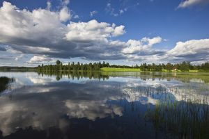 Cumulus clouds in blue sky reflected in Norrmogen Lake