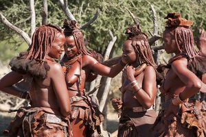 Group of Himba women who have covered their skin, and hair, with a mixture of ochre and butter fat