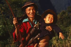 Himalayan man from Gasheng village holding young boy.