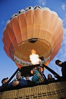 Hot air balloon in flight with group of passengers in the gondola,