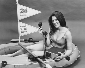 March 1973: young woman in raft holding a ship to shore radio