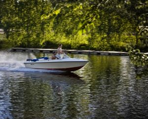 Motorboat speeding along river in summer,