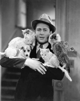 Movie actor James Dunn (1901-1967) with an armful of cats and dogs in the film Handle With Care