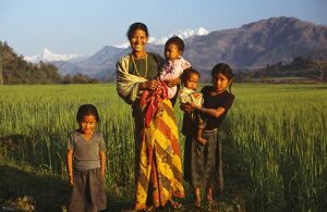 Nepalese family standing beside rice crop.