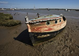 Old wooden boat hauled out on mud flat,