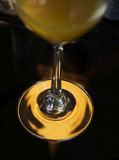 Orange juice in wine glass with focus on stem and base,