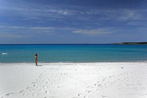 Porto Pino beach with a beachgoer standing on the white sand.