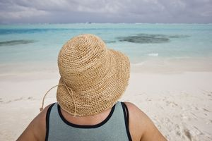 Rear view of tourist wearing straw hat on Maadhoo Finolhu or Picnic Island,