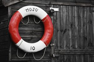 Red and white lifebuoy hanging on timber wall,