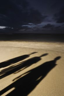 Shadows of three people on the beach at night