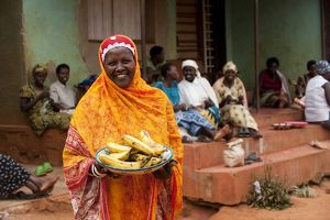 A smiling Muslim woman with bright headscarf holding a basket of bananas