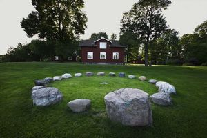 Stone circle in front of timber house,