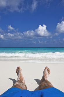 Sunbakers feet on white sand beach at Petite Anse,