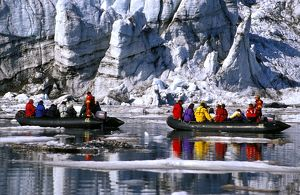 Tourists in zodiacs viewing snout of glacier,