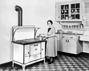 Vintage photograph from 128 of a woman in her modern kitchen using the Monarch Oven