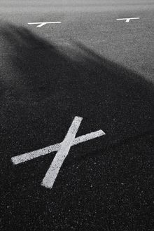 A white painted letter X on the road surface of a carpark,