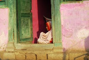 Woman at the window opening of her village home