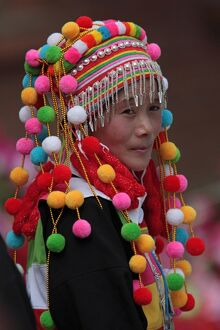 A young woman dancer of the Lisu minority people wearing a traditional headdress.