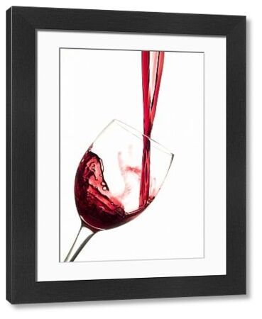 Red wine being poured into glass, studio photograph with white background