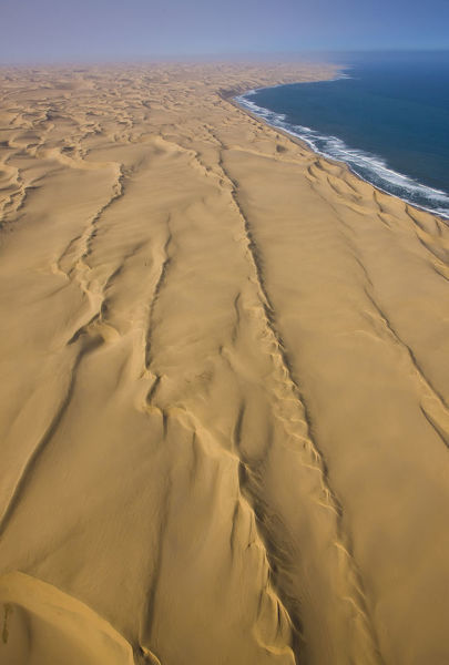 Aerial view of coastal dunes of the Namib Sand Sea, a World Heritage region, with the Atlantic Ocean in the distance