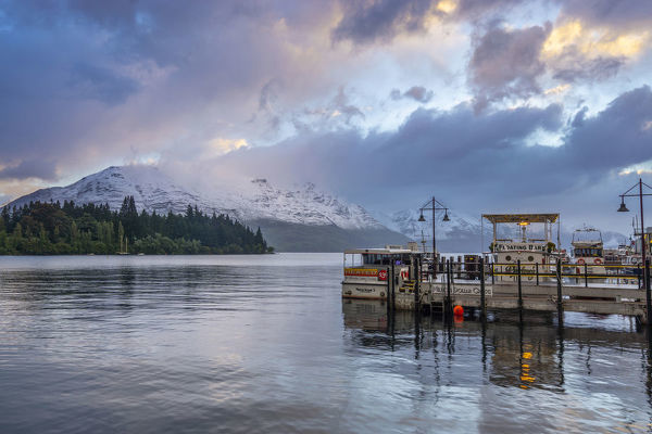Lakeside scene at dusk in Queenstown, town that is a centre for snow sports and in summer a focus of adventure tourism including bungy jumping, mountain biking, whitewater rafting and jet boating. Queenstown, Central Otago, South Island, New Zealand